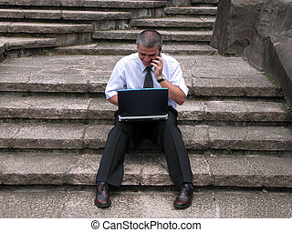 Working on rocks stairs - Man working with computer and...
