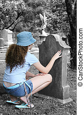 Girl In Graveyard 1 - a young girl lookin at a tombstone in...
