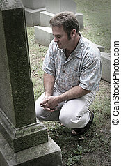 Grief - a man in a graveyard with hands folded in reverence...