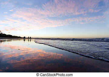 People at the beach - during sunset at Noosa, Australia