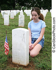 In Mourning - a girl in a military graveyard, mourning a...