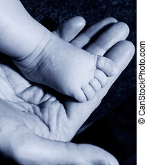 Baby foot on mans hand in blue