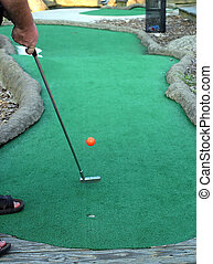 I Got Game - A man putting on a miniature golf course