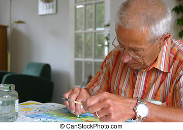 Older man painting - Older man busy with his painting