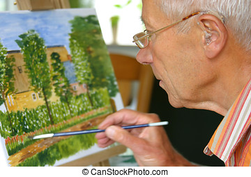 Older man painting - Older man working on his painting