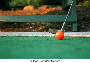 Poised To Putt - A putter and mini-golf ball.