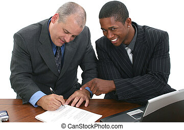 Businessmen Signing Contracts - Two men in suits at desk...