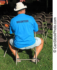 Volunteer - a volunteer sitting outside a concert tent at a...
