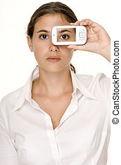 Eye On The Phone - A young woman holds a smartphone to her...