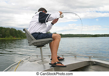 gone fishing - A man catches a fish from the front of his...