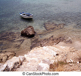 OLD ROW BOAT - stone tile steps leading to the shore with an...