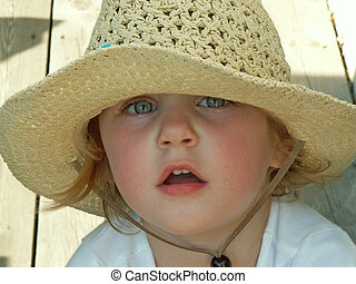 shaded from the sun - little girl wearing sunhat, soft focus...