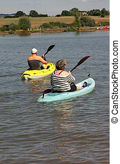 Mature couple canoes - Mature couple in a pair of canoes on...