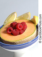 fruit - fresh cantaloupe filled with red raspberries with...