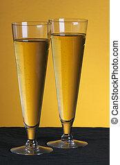 Pilsner glasses - two pilsner glasses on a golden backdrop
