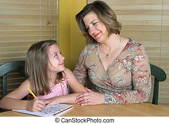 Helping With Homework 1 - A mother helping her daughter do...