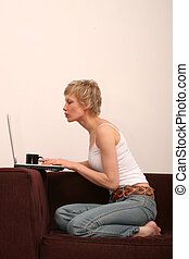 woman checking www - Pretty woman sitting on sofa with cup...