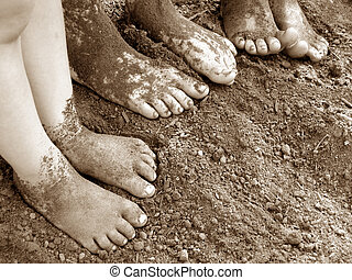 Bath Time 1 - Three small pairs of feet in a pile of dirt