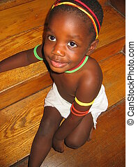 African child. - Small, decorated African child sitting on...