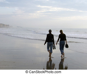 Summer stroll - Two women walking on beach in Ostend,...