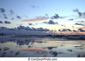 Mirror beach - Sunset sky reflected at the wet sand of the...
