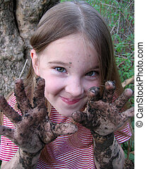 Mud Pies - Little girl with impish grin and very muddy...