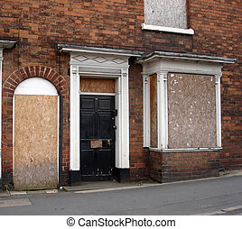 Boarded up house - Derelict building with boards over the...