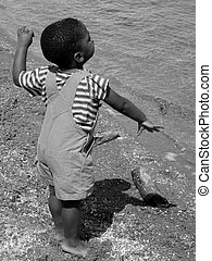 Throwing pebbles. - Little boy throwing pebbles into the...