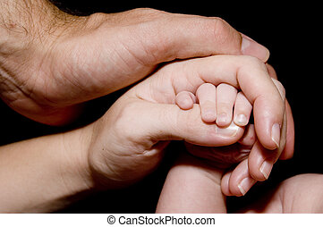 New family - Mum and Dad hold the hand of a new baby