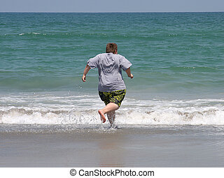 Eager To Swim - a boy at the beach, running to swim in the...