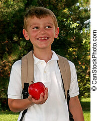 first day of school - boy taking an apple for his teacher on...