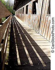 Four Shadows - Shadowed walk on covered bridge