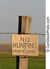 no hunting sign on wooden post with barbed wire