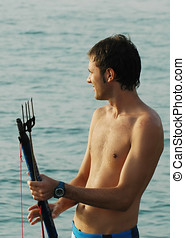 Man with harpoon - Young man holding under water fishing...