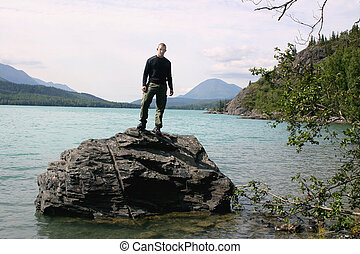 On Top - A young man stands on top of a boulder in a...