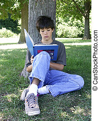 boy reading - teen boy reading a book under a tree