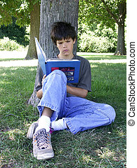 boy reading - teenager reading a book under a tree