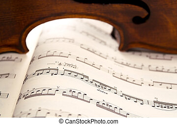 Light through violin's ribs on music score - Light shines...