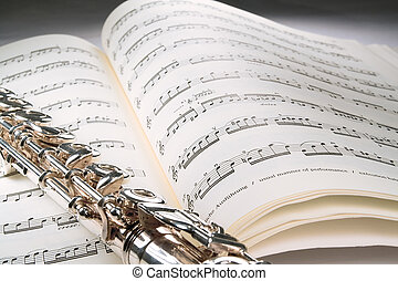 Flute on an open musical score with gray background - A...
