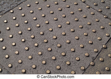 Studs in sidewalk - Close-up of brass studs as hazard...