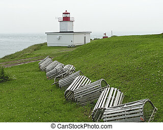 lobster traps sitting on the grass near a lighthouse in New...