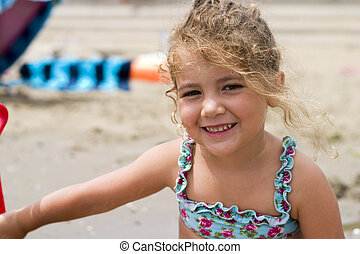 happy little girl on the beach - little girl playng happily...