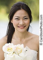 Asian Bride 6 - A beautiful young woman poses by a lake in a...