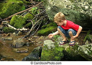 Squatting - A little boy playing next to a creek.
