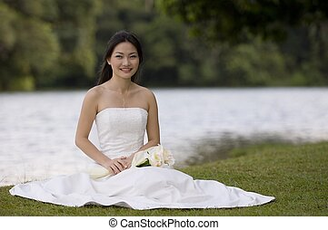 Asian Bride 11 - A beautiful asian bride sits by a lake in...