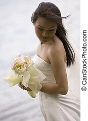 Asian Bride 18 - A beautiful asian woman poses by a lake in...