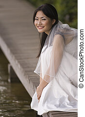 Outdoor Bride 6 - A beautiful asian bride sits on a...