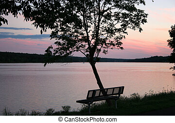 Empty Bench At Sunset - An empty bench overlooking the lake...