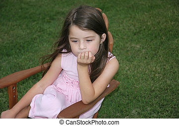Children - Lonely Girl - Sad little girl sits in a chair on...