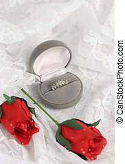 Roses & Romance Vertical - a wedding ring and silk roses on...